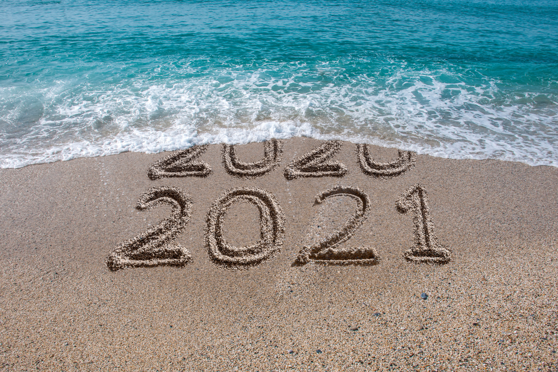2020 turning into 2021 on a beach