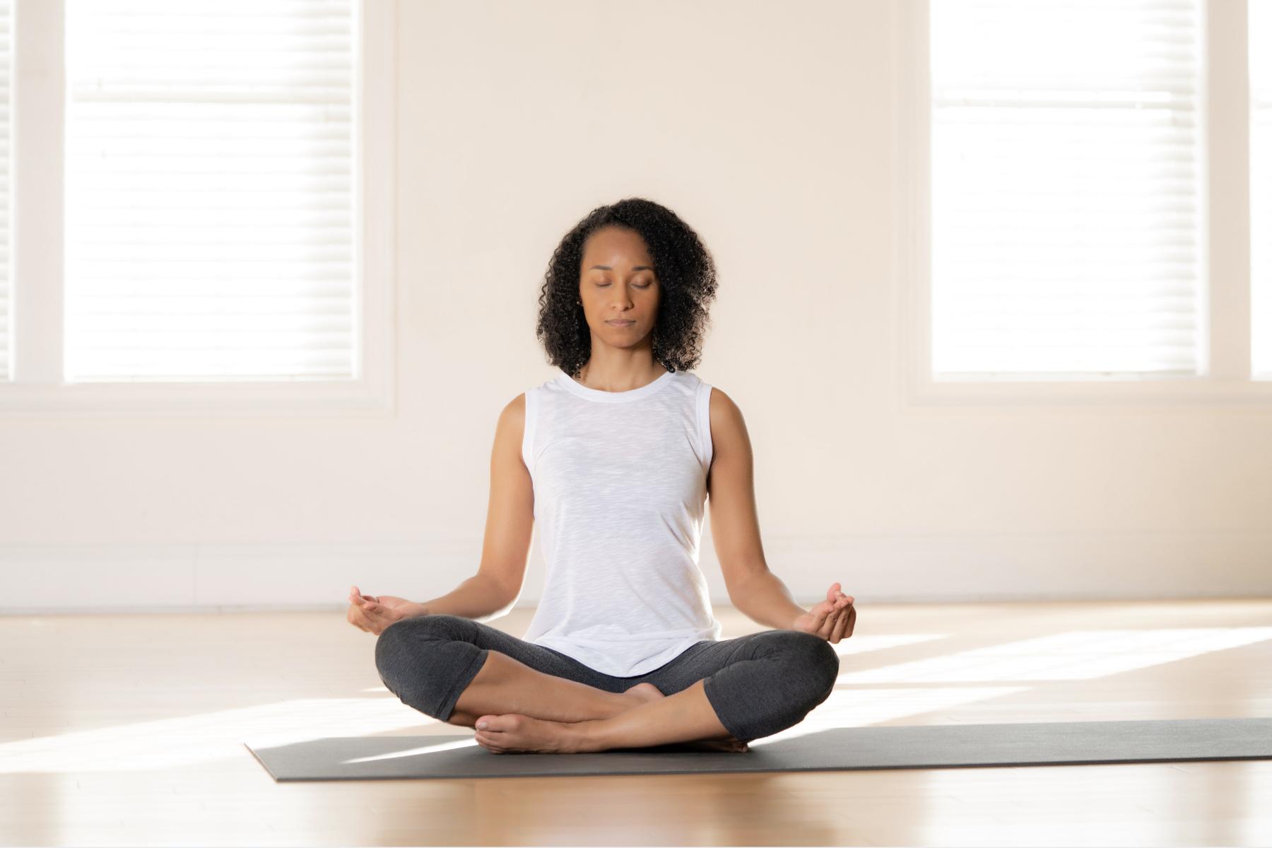 woman meditating on a mat