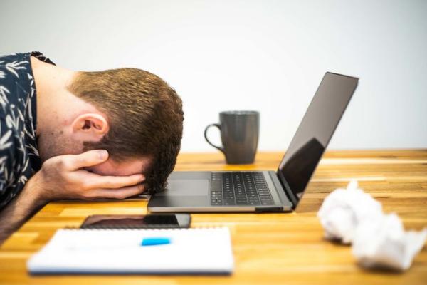 man tired at his laptop