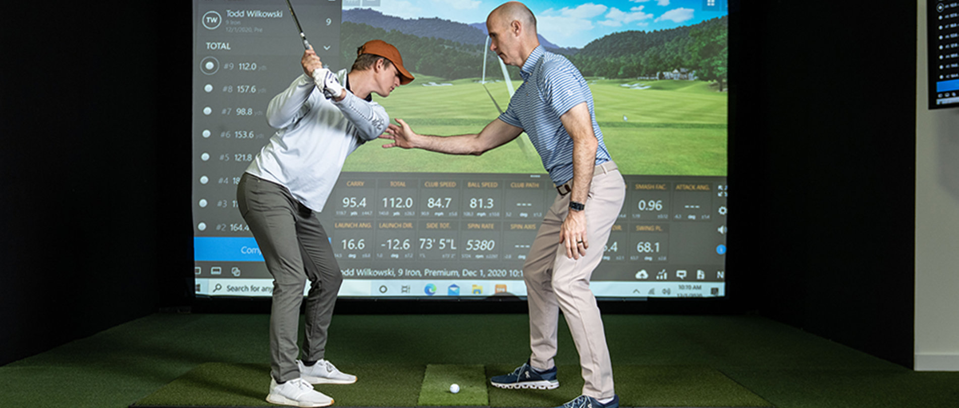 trainer coaching a client on the golf simulator