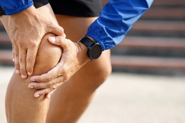 man holding knee during a run in pain