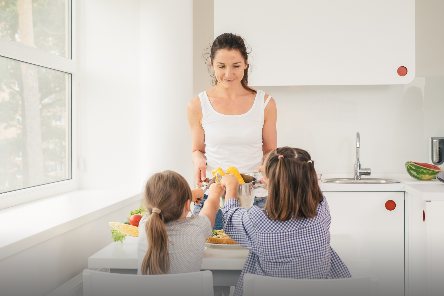 Mother serving food to two daughters