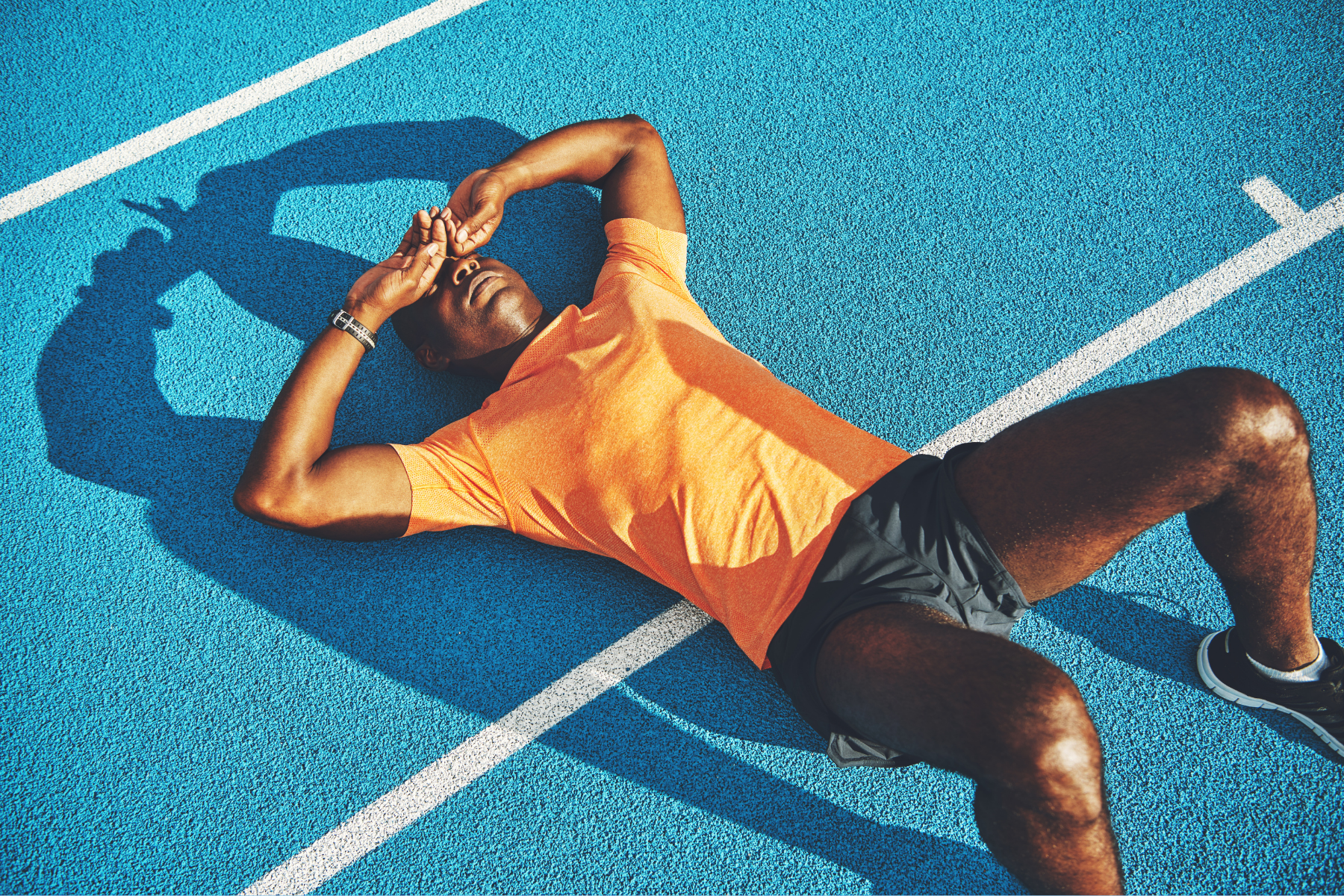 Runner tired and laying down on the track
