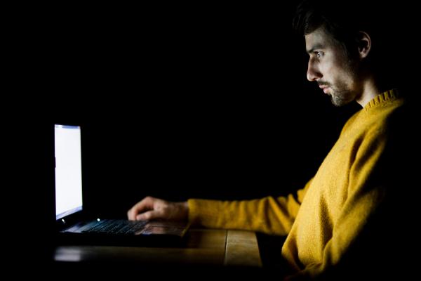 man at his computer at night