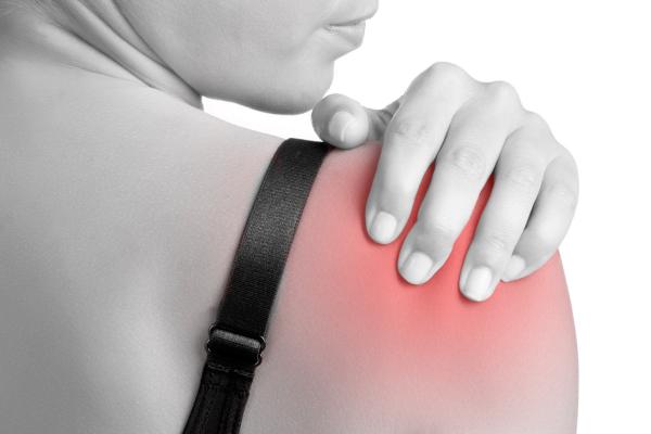 Woman holding her injured shoulder
